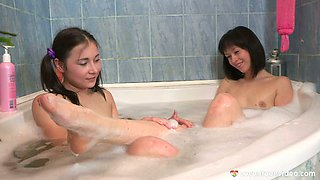 Two adorable teens are bathing in bubbly spa