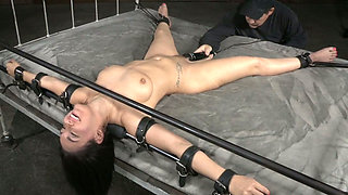 Crucified on the wide bed busty brunette is fucked with black toy