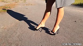 Walking in black high heeled mules