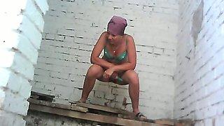 White chick in green bikini pisses in the public toilet room