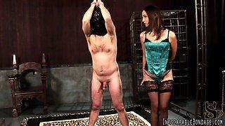 Lingerie-clad dominatrix with long dark hair torturing a stranger