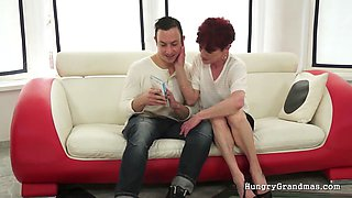 A handsome young stud is seducing a redhead granny and give her his stiff cock
