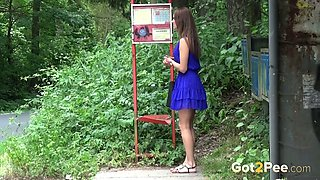 Brunette hottie on the bus stop spraying urine in the bushes