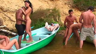 Horny people are having group sex on the beach in a small boat